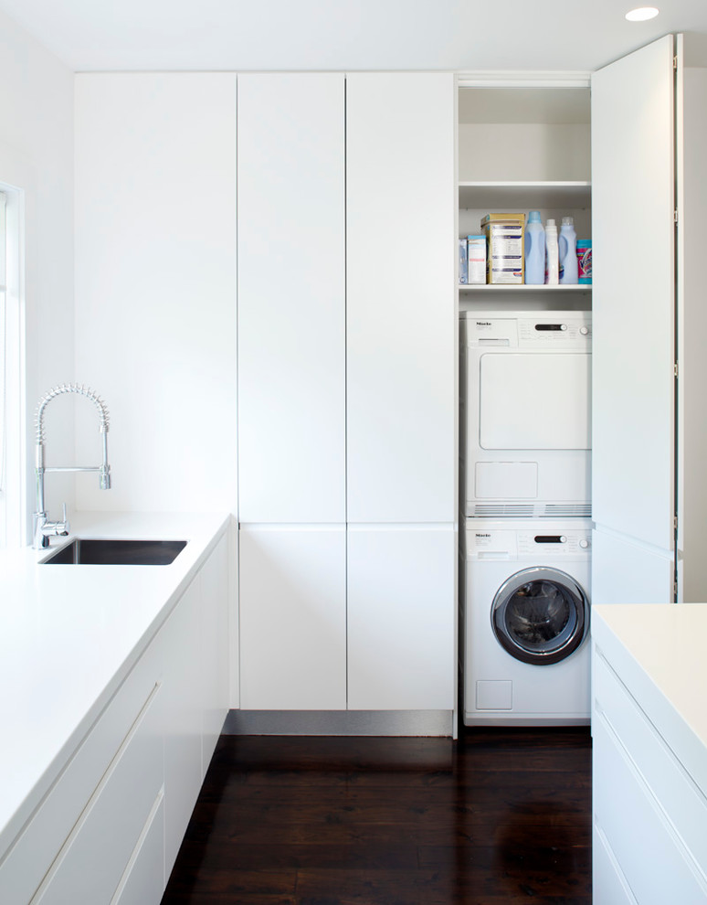 Minimalist laundry room photo in Sydney with white cabinets and a concealed washer/dryer