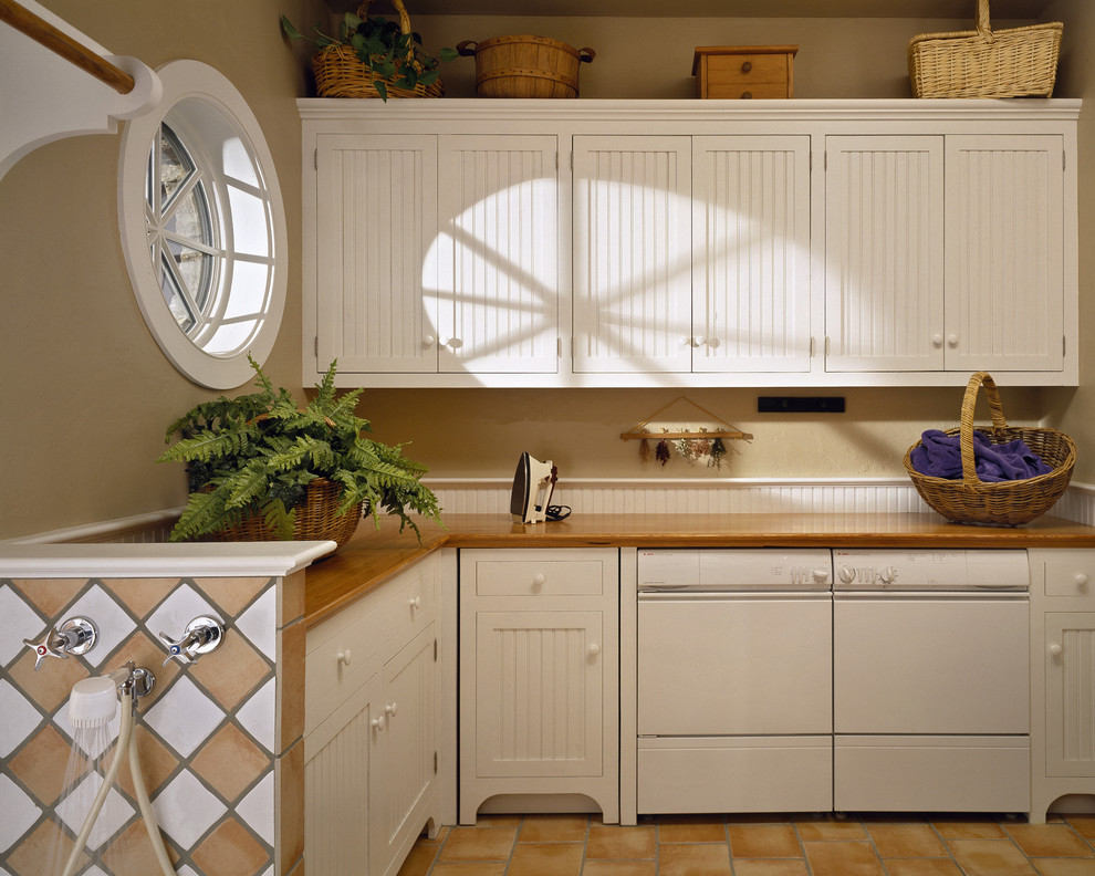 Example of a classic laundry room design in New York with white cabinets