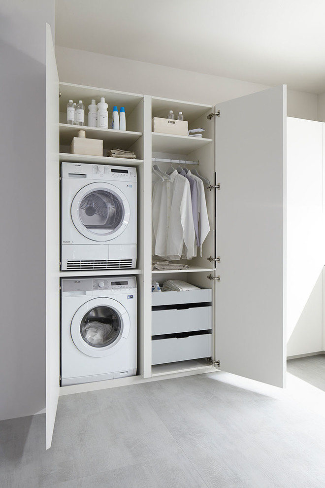 Example of a small trendy single-wall laundry room design in Other with flat-panel cabinets, white cabinets, white walls and a stacked washer/dryer