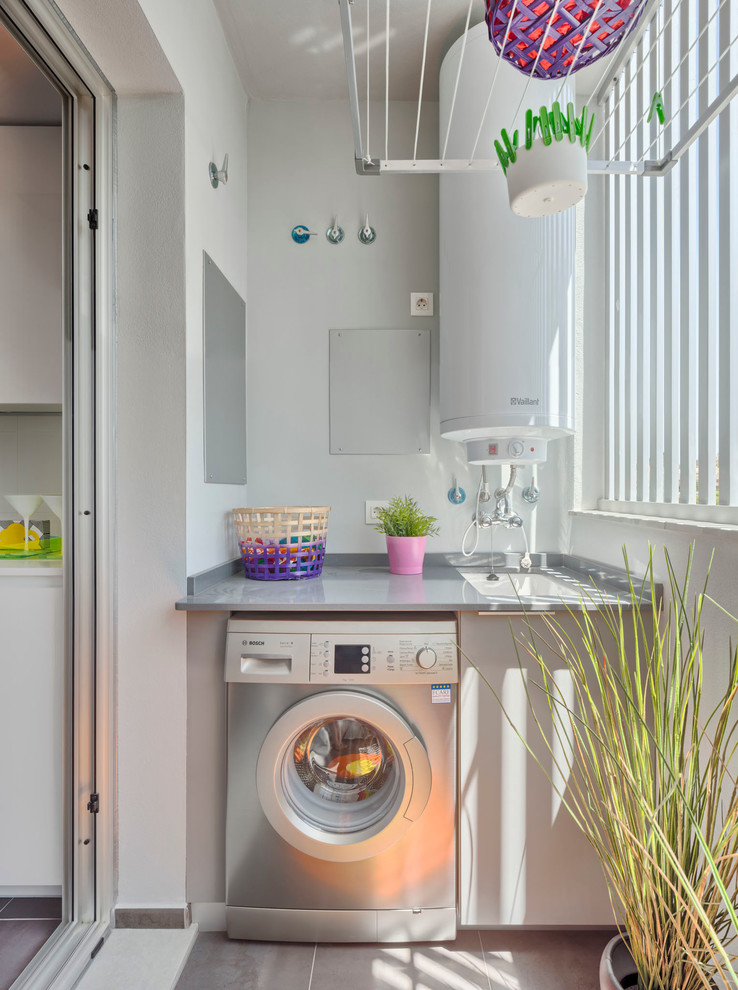Example of a mid-sized eclectic single-wall dedicated laundry room design in Malaga with an undermount sink, flat-panel cabinets, gray cabinets, white walls, a side-by-side washer/dryer and gray countertops