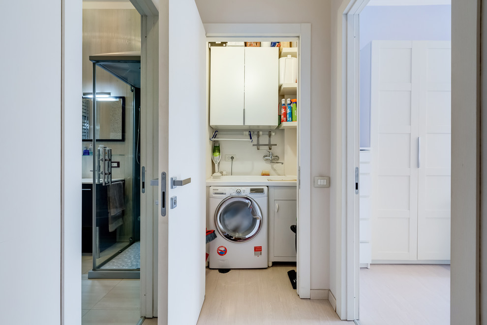 Small minimalist laminate floor and beige floor utility room photo in Rome with flat-panel cabinets, white cabinets, beige walls and a side-by-side washer/dryer