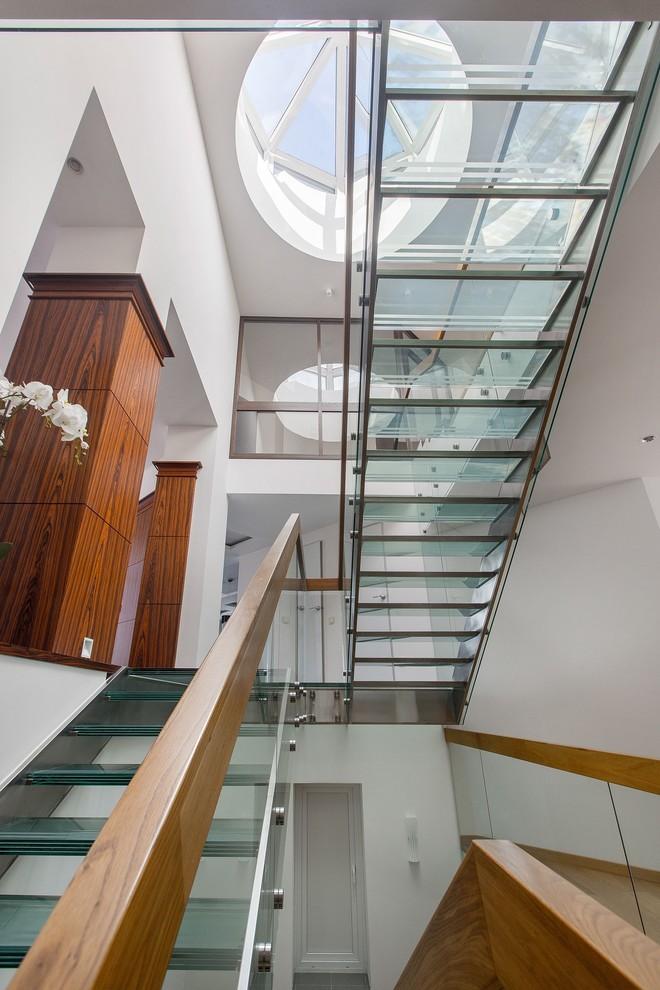 На фото: п-образная лестница в современном стиле с стеклянными ступенями и перилами из смешанных материалов без подступенок с