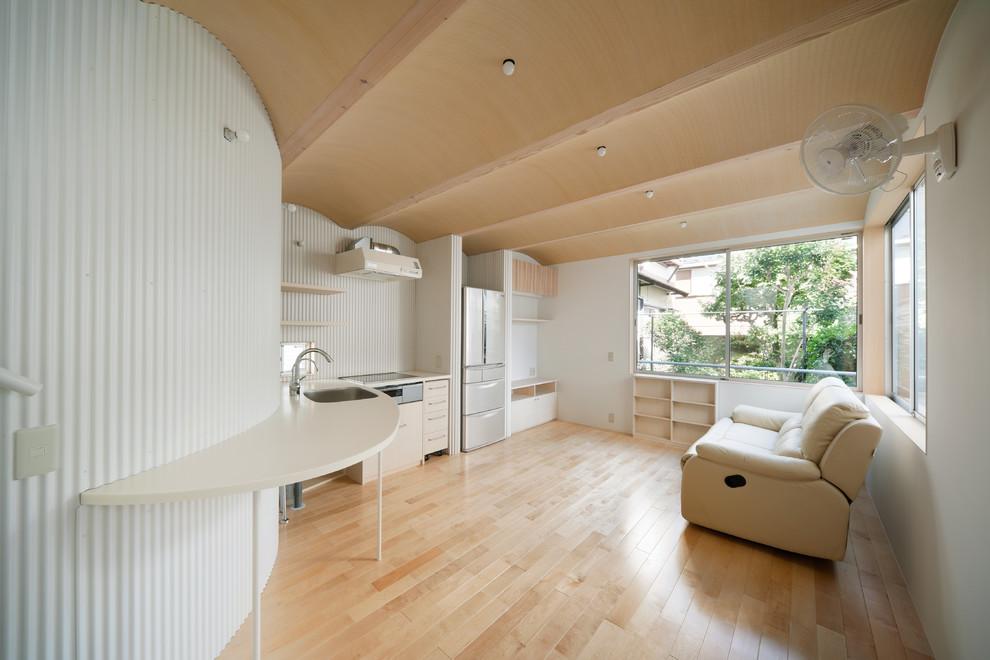 Small scandinavian open plan living room with white walls, light hardwood flooring, a freestanding tv and beige floors.