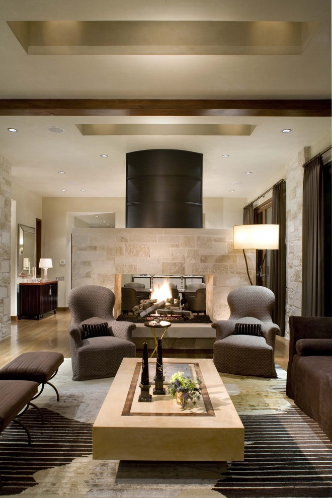 Example of a mid-century modern living room design in Denver with a two-sided fireplace