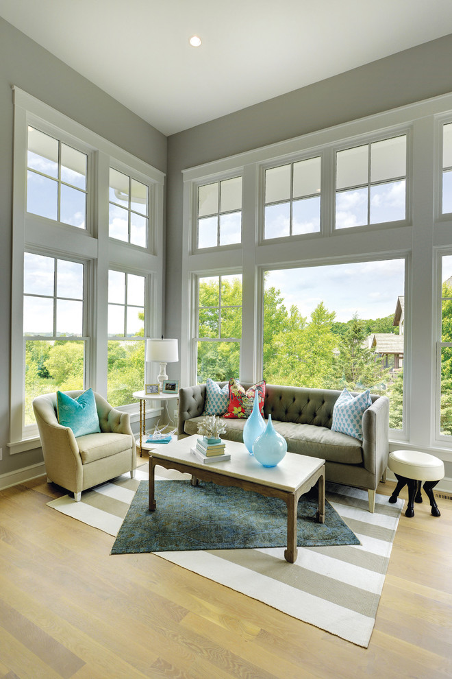 Transitional open concept medium tone wood floor living room photo in Minneapolis with gray walls