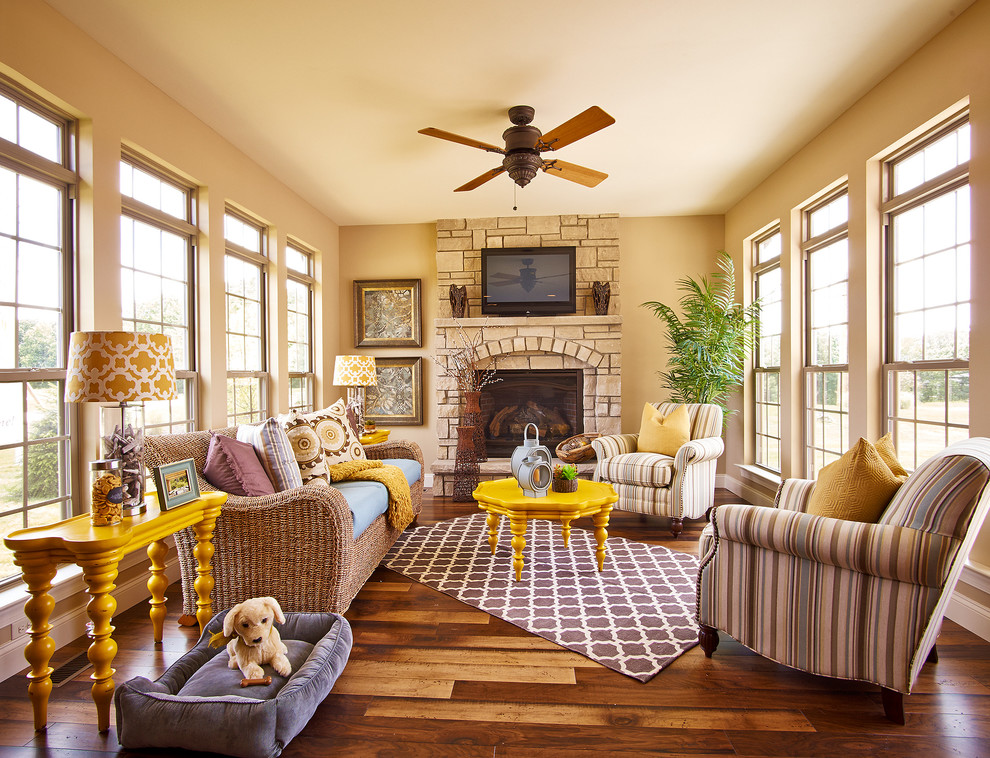 Inspiration for a mid-sized timeless dark wood floor living room remodel in St Louis with beige walls, a standard fireplace, a stone fireplace and a wall-mounted tv