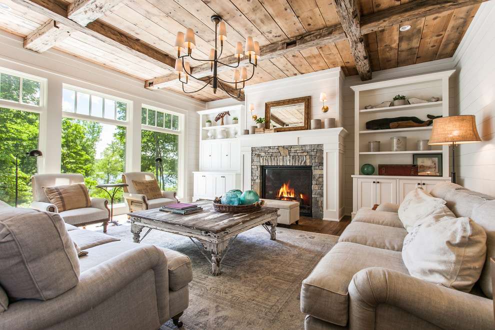 Inspiration for a farmhouse formal and open concept medium tone wood floor and brown floor living room remodel with white walls, a standard fireplace, a stone fireplace and no tv