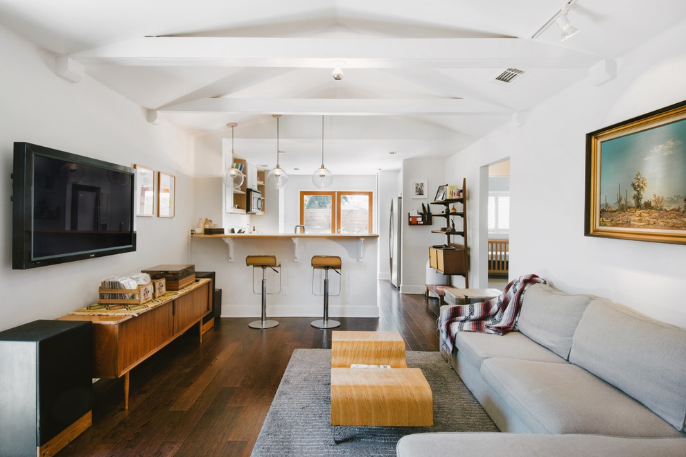 Inspiration for a 1960s open concept dark wood floor living room remodel in Orange County with white walls and a wall-mounted tv