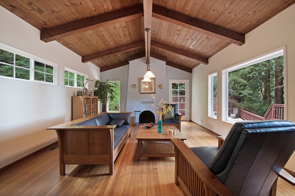 Example of a tuscan formal medium tone wood floor living room design in San Francisco with white walls, a standard fireplace, a plaster fireplace and no tv