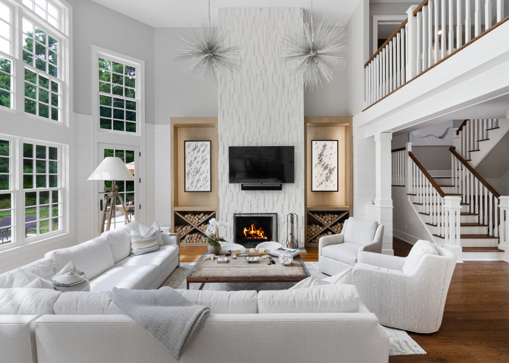 Large transitional formal and open concept medium tone wood floor and brown floor living room photo in New York with white walls, a standard fireplace and a wall-mounted tv