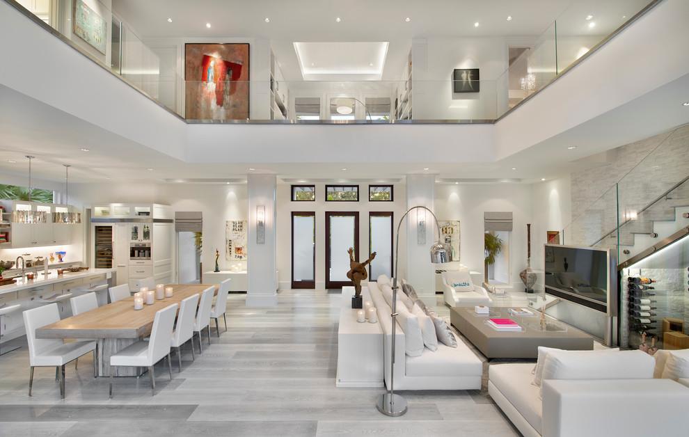 Modelo de salón para visitas abierto, contemporáneo, con paredes blancas, suelo de madera clara, televisor independiente y suelo gris