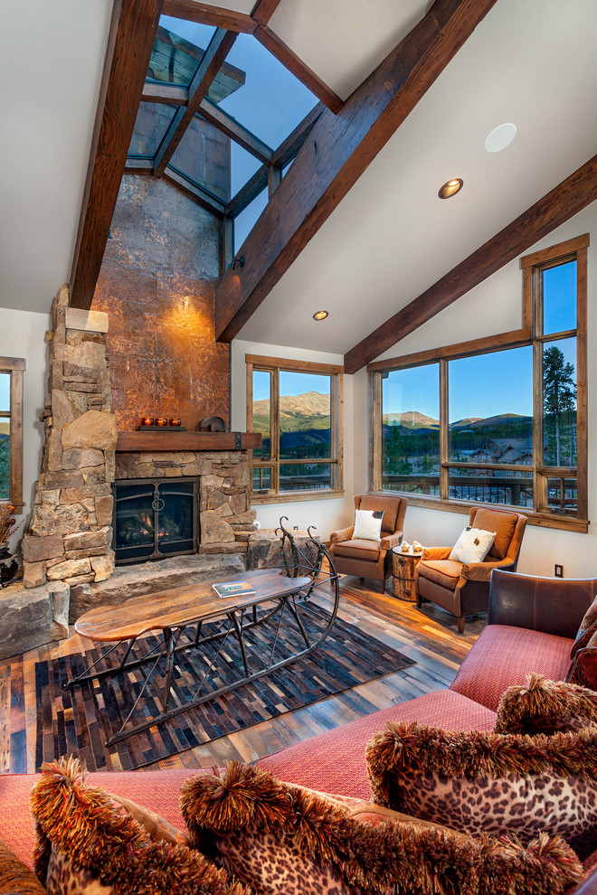 Inspiration for a rustic dark wood floor living room remodel in Denver with white walls, a standard fireplace and a stone fireplace