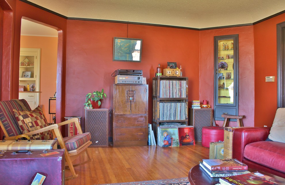Example of an eclectic enclosed medium tone wood floor living room design in Seattle with red walls, a standard fireplace and a tile fireplace