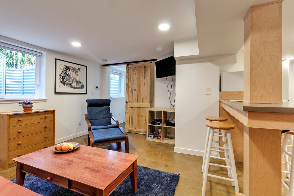 Small minimalist open concept concrete floor and beige floor living room photo in Portland with beige walls, no fireplace and a wall-mounted tv