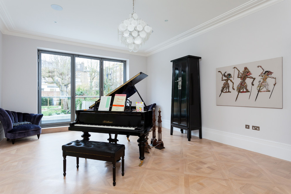 Large transitional light wood floor living room photo in London with a music area, white walls, no fireplace and no tv