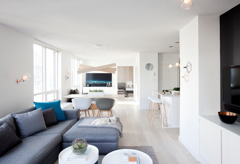 Example of a small danish formal and open concept light wood floor living room design in Vancouver with white walls and a wall-mounted tv