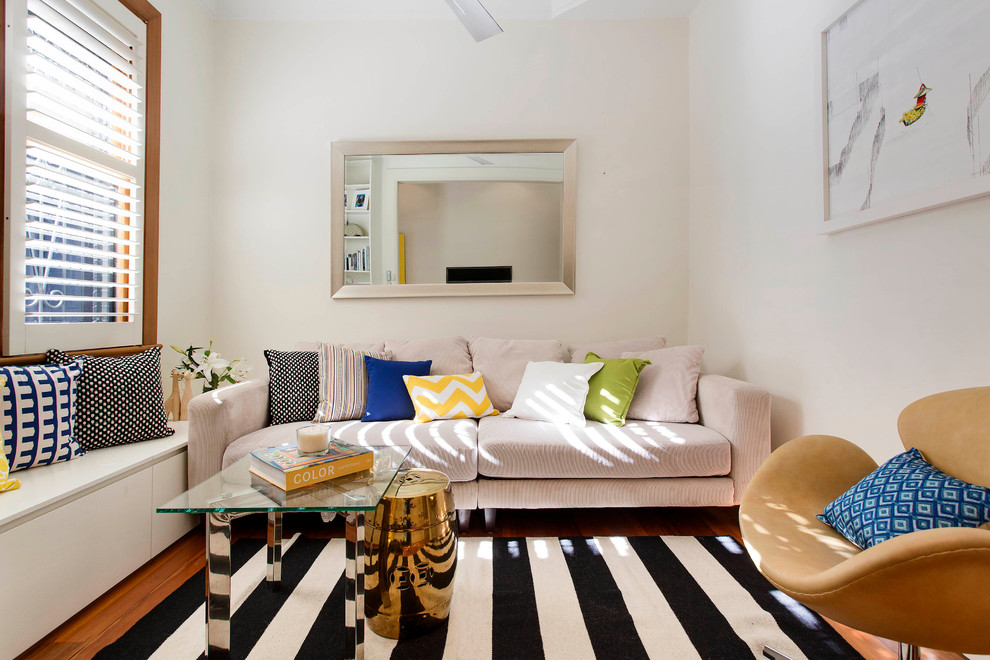 Example of a small transitional formal medium tone wood floor living room design in Sydney with white walls and no tv