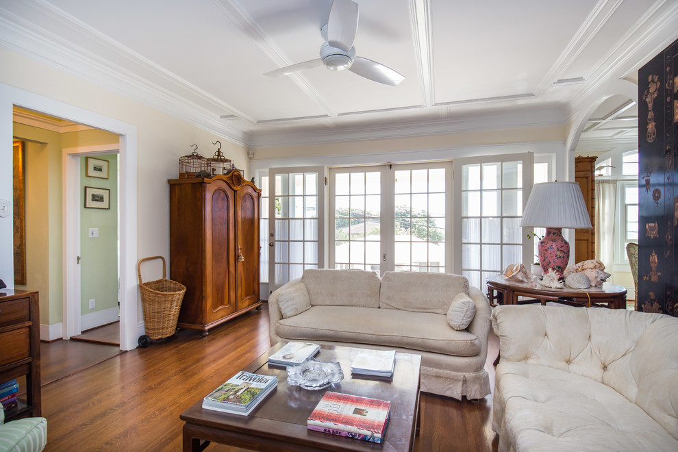 Example of a large classic formal and open concept medium tone wood floor living room design in Hawaii with beige walls
