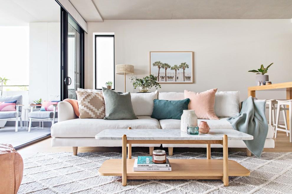 Small danish open concept light wood floor and beige floor living room photo in Sydney with white walls