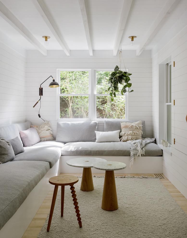 Living room - scandinavian enclosed light wood floor living room idea in New York with white walls