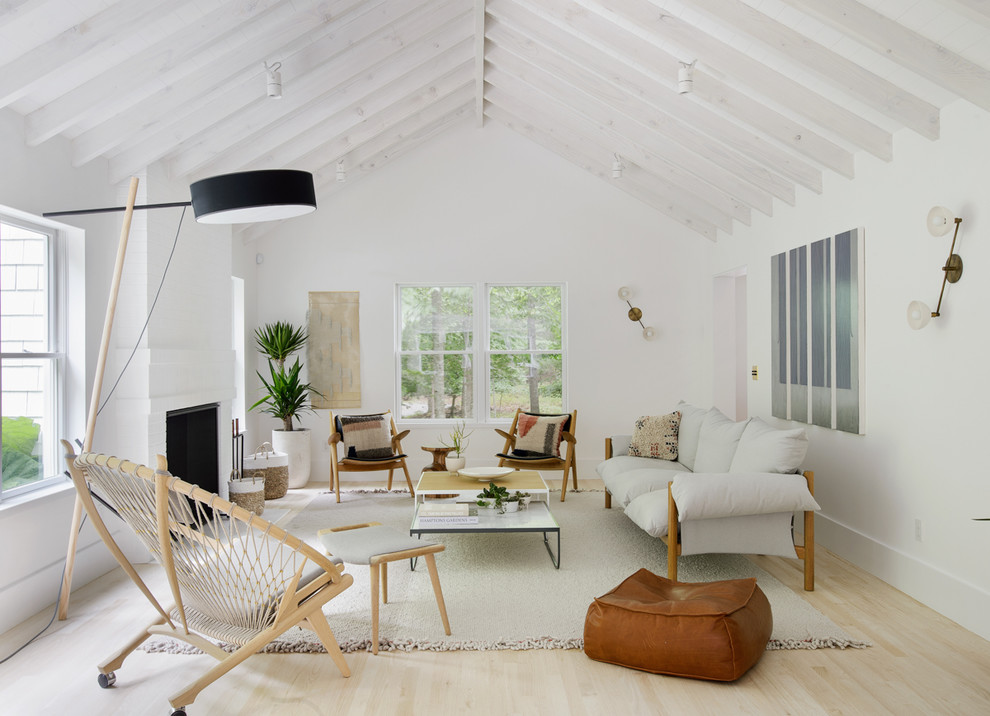 Living room - scandinavian enclosed light wood floor living room idea in New York with white walls and a standard fireplace
