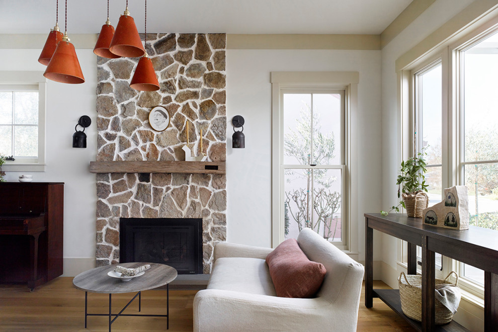 Inspiration for a mid-sized cottage medium tone wood floor living room remodel in San Francisco with a standard fireplace and a stone fireplace