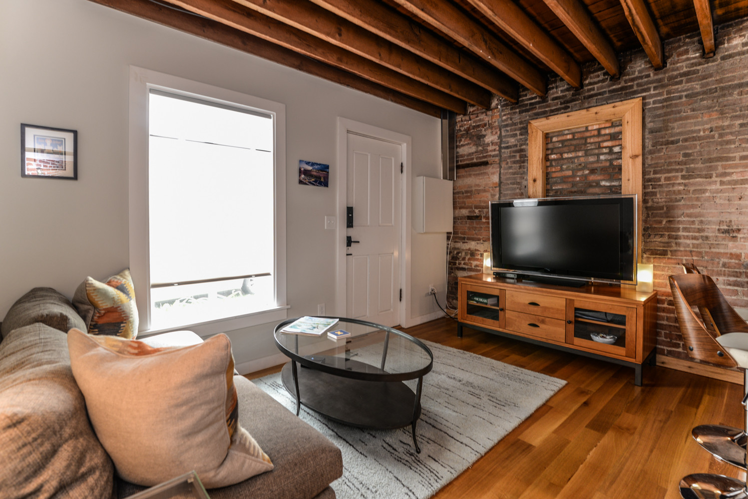 The exposed wood beams and brick give instant warmth to the carriage house loft. Reclaimed wood floors with a natural clear coat finish provide just enough color to the neutral palette of furniture an