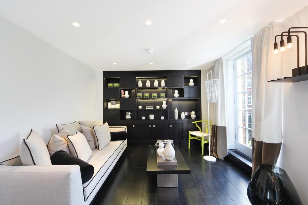 Large trendy dark wood floor and black floor living room photo in London with white walls