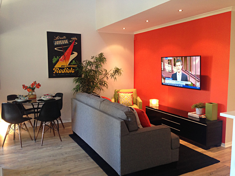 Example of a mid-sized minimalist open concept bamboo floor living room design in Brisbane with orange walls and a wall-mounted tv