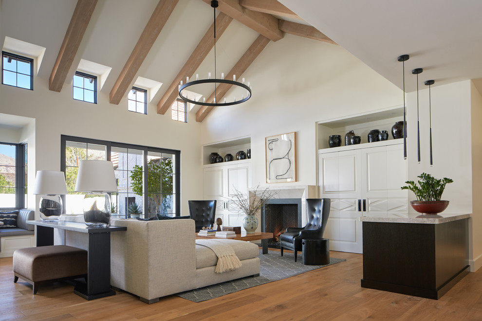 Example of a transitional medium tone wood floor and brown floor living room design in Phoenix with white walls and a standard fireplace