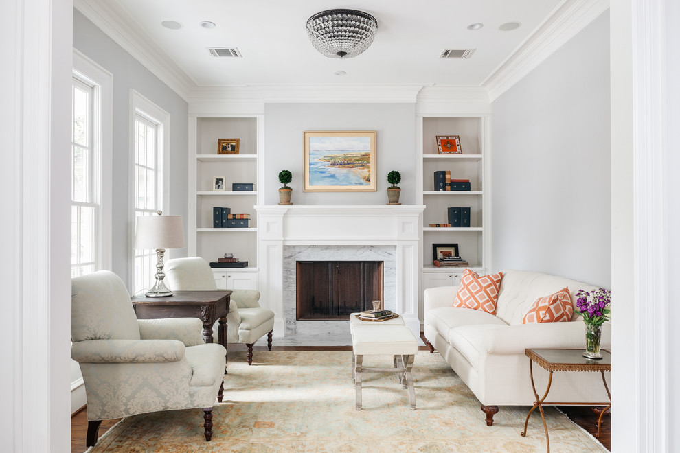 Elegant formal medium tone wood floor living room photo in Houston with blue walls, a standard fireplace and a stone fireplace