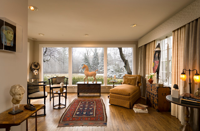 Example of a mid-sized eclectic enclosed dark wood floor and brown floor living room design in Chicago with beige walls, no fireplace and no tv