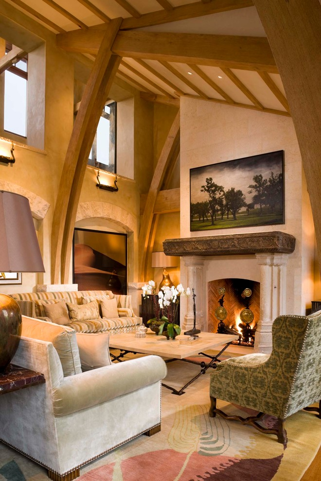 Inspiration for a large mediterranean formal and open concept medium tone wood floor living room remodel in Denver with beige walls, a standard fireplace, a stone fireplace and no tv