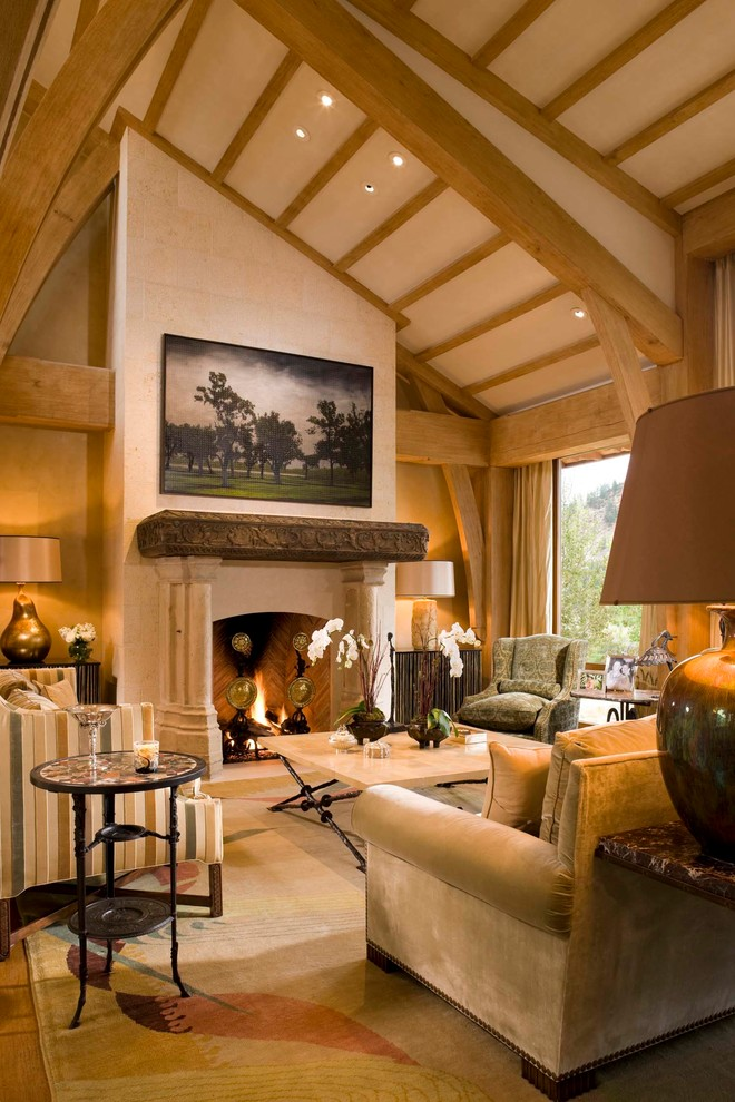 Large tuscan formal and open concept medium tone wood floor living room photo in Denver with beige walls, a standard fireplace, a stone fireplace and no tv