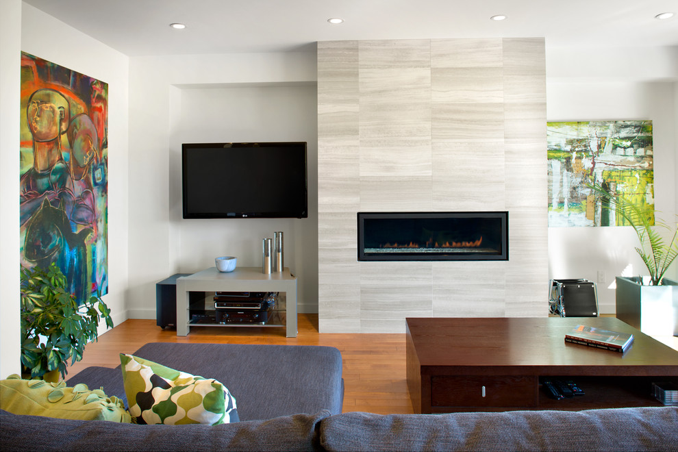 Living room - modern open concept medium tone wood floor living room idea in Vancouver with a ribbon fireplace, a wall-mounted tv, white walls and a stone fireplace