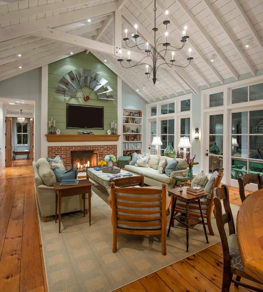 Example of a cottage open concept medium tone wood floor living room design in Dallas with gray walls, a standard fireplace, a brick fireplace and a wall-mounted tv