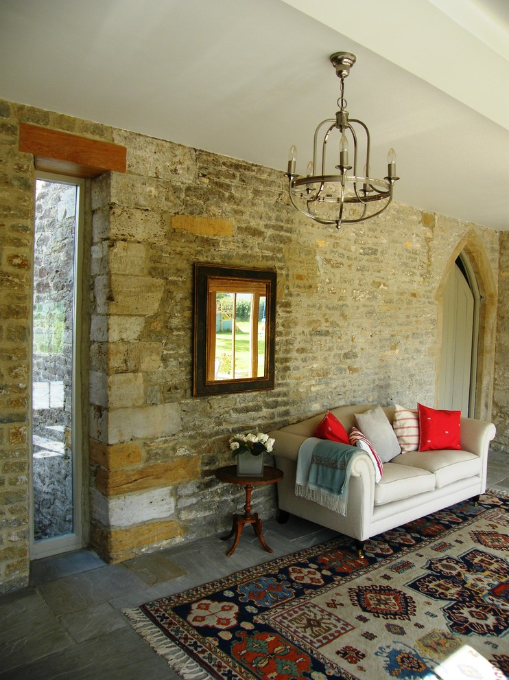 Farmhouse slate floor living room photo in Dorset with beige walls