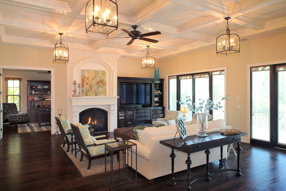 Example of a tuscan living room design in Tampa with beige walls, a standard fireplace and a media wall