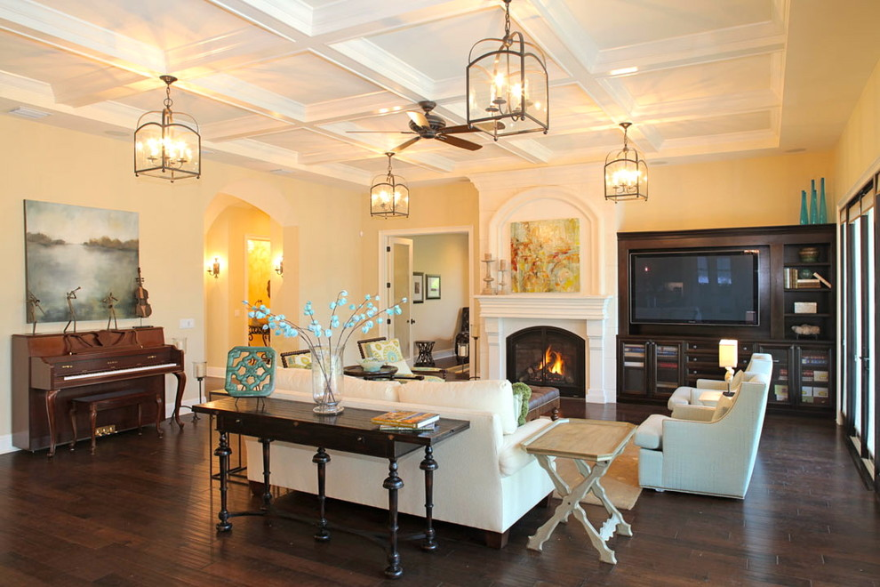 Tuscan living room photo in Tampa with beige walls, a standard fireplace and a media wall