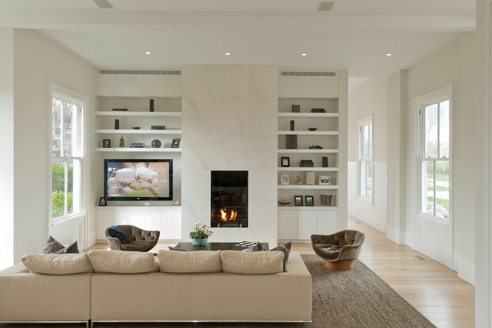 Inspiration for a coastal light wood floor living room remodel in New York with white walls and a standard fireplace