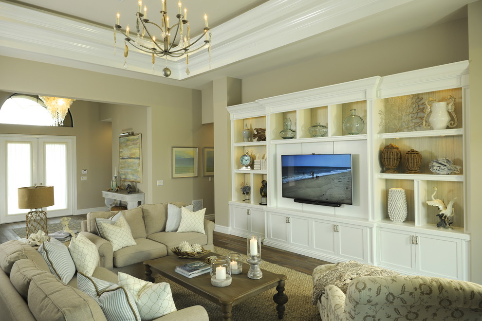 Inspiration for a coastal medium tone wood floor living room remodel in Miami with beige walls and a wall-mounted tv
