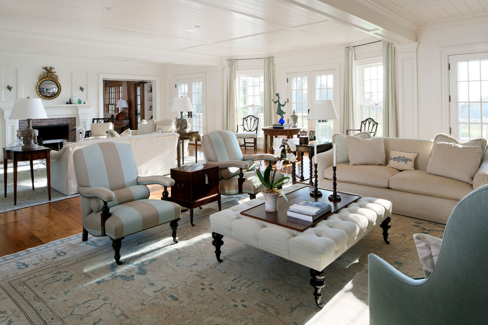 Beach style open concept medium tone wood floor living room photo in Boston with white walls