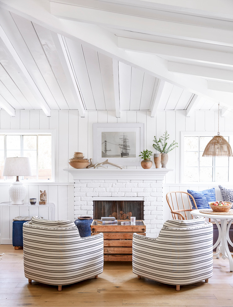 Inspiration for a small coastal open concept light wood floor living room remodel in Los Angeles with white walls, a standard fireplace, a brick fireplace and no tv