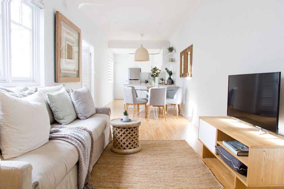 Inspiration for a scandinavian open concept light wood floor living room remodel in Sydney with white walls, no fireplace and a tv stand