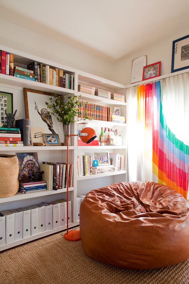 Eclectic living room library photo with white walls
