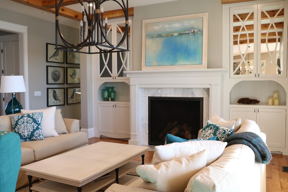 Living room - large country open concept medium tone wood floor living room idea in Other with gray walls, a standard fireplace, a wood fireplace surround and a media wall