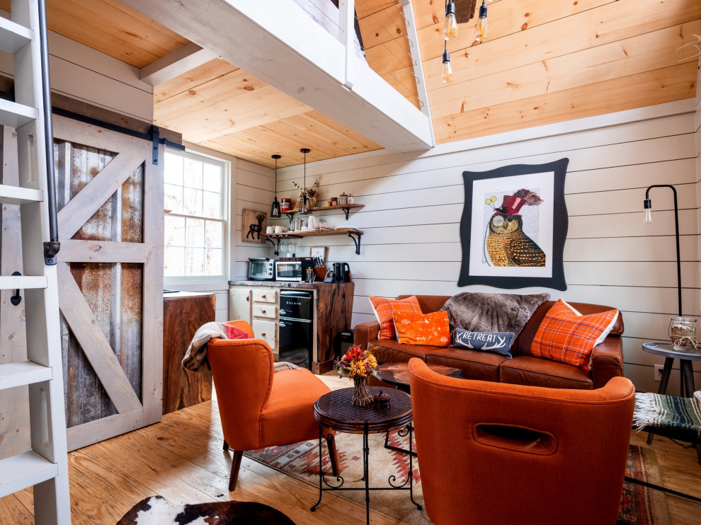 Inspiration for a small rustic medium tone wood floor, brown floor, vaulted ceiling and shiplap wall living room remodel with white walls