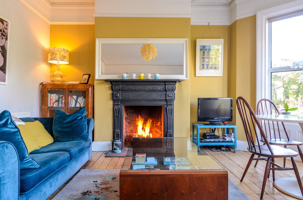 Inspiration for an eclectic medium tone wood floor living room remodel in Belfast with yellow walls, a standard fireplace and a tv stand