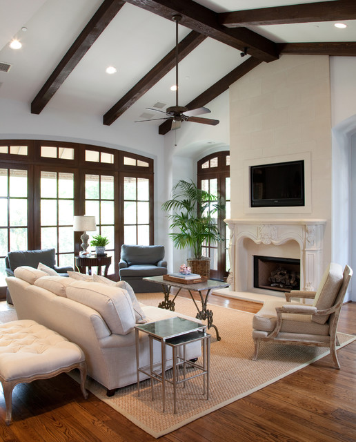 This is an example of a mid-sized traditional living room in Houston with medium hardwood floors, a standard fireplace, a wall-mounted tv and white walls.