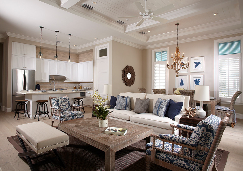 Example of a beach style open concept light wood floor and gray floor living room design in Miami with beige walls